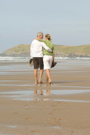 Couple walking arm in arm on a beach