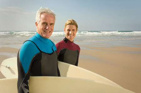 Couple with surfboards on a beach Banco de Imagens - 113892976