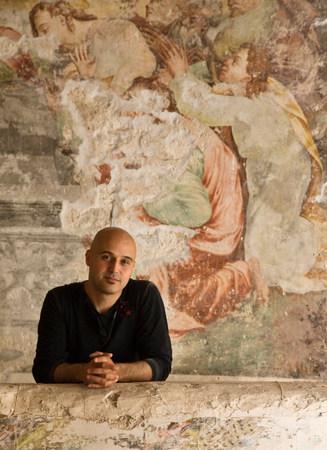Man standing in front of fresco