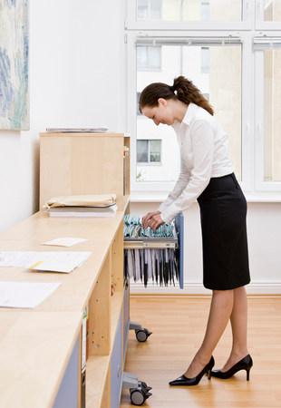Woman working on filing paperwork Foto de archivo
