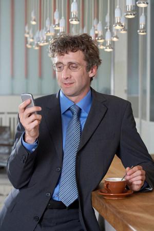 Businessman at bar looking at his mobile