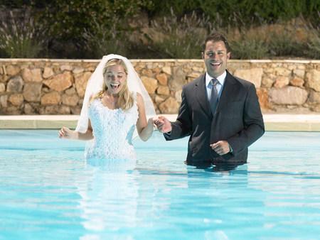 Bride and groom standing in pool Banco de Imagens