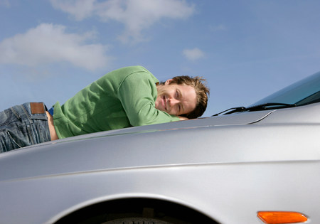 Man lying on car