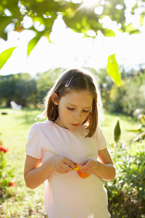 Young girl outside eating fruit Banque d'images