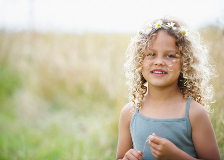 Young girl with daisies in hair Stock Photo