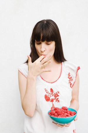 Woman tasting raspberries