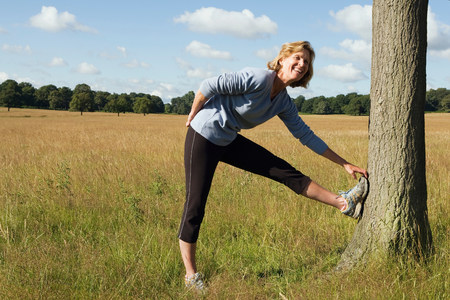 Woman runner stretching against tree Imagens