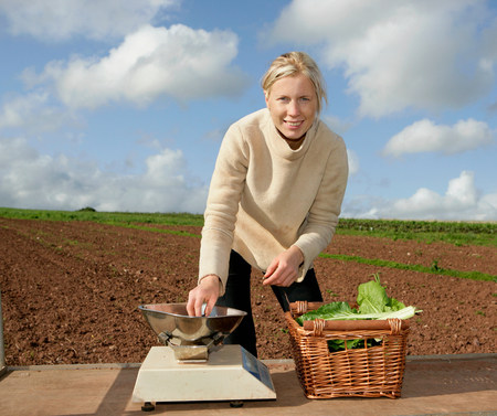 farm worker weighs crops