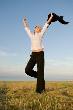 Business woman in a field with arms up