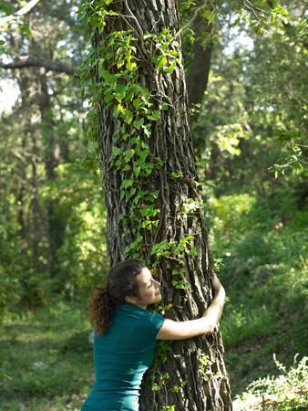 Young woman hugging tree Reklamní fotografie