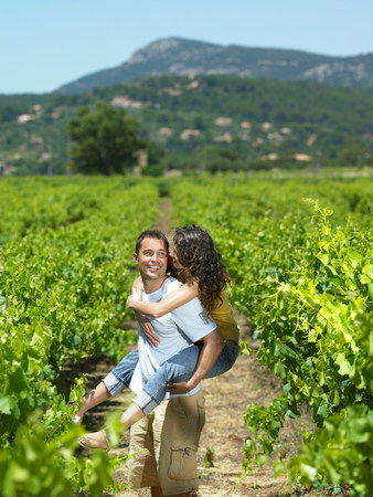 Man carrying woman in vineyard 写真素材