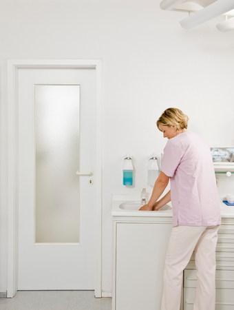 Female dentist washing her hands Stock Photo