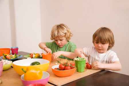 Two boys cutting vegetables