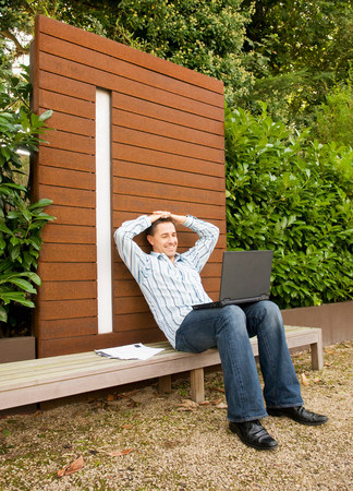Businessman relaxing with laptop outside