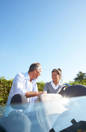 Mature couple putting bags into car Stock Photo