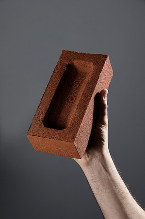 Male hand holding a brick