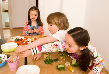 Two girls and boy cooking vegetables