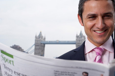 Business man reading news paper outside Stock Photo