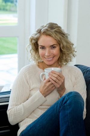Woman on sofa with cupmug