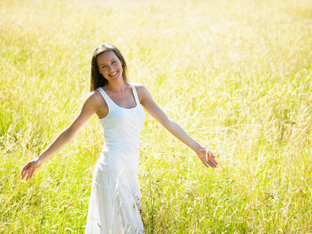 Woman walking in a field,  smiling Stock Photo