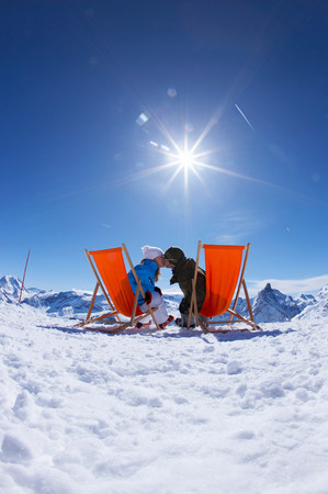 Couple kissingreclining in deck chairs