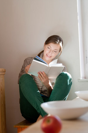 Woman in kitchen reading