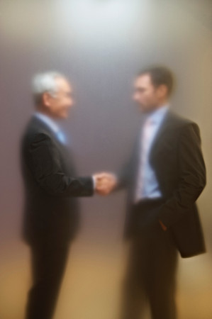Men shaking hands behind frosted screen