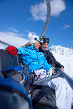 Couple sitting close in chair lift 免版税图像