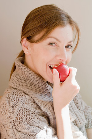 Woman smiling at viewer eating an apple