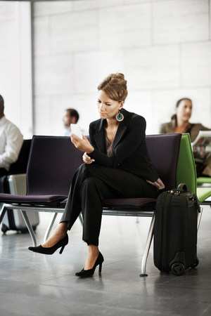 Woman holding cellphone, waiting