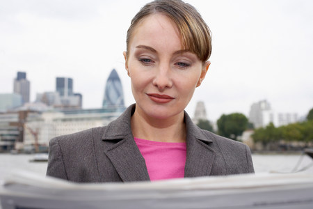 Business woman reading newspaper outside Imagens