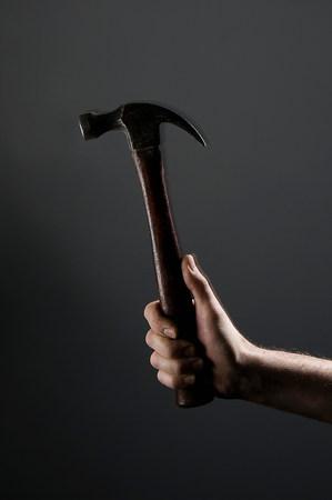 Female hand holding a hammer