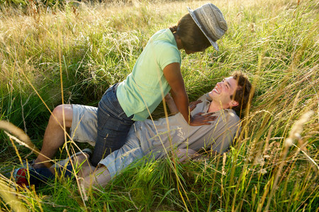 Couple fooling around in a field
