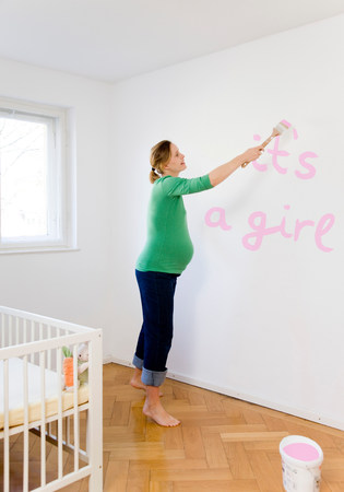 Pregnant woman painting nursery 免版税图像
