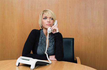 Woman on phone in boardroom 免版税图像