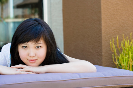 Teen relaxing on lounge chair outside