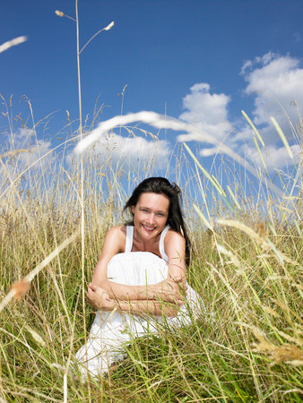 Woman seated in a field,  smiling 免版税图像