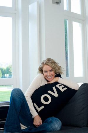 Woman on sofa with cushion