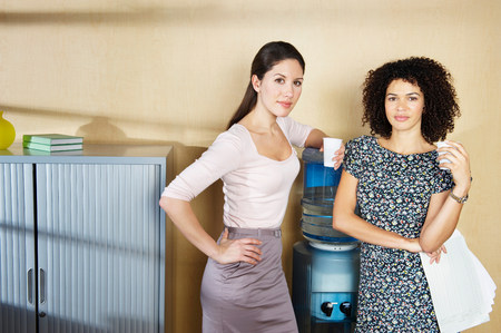 Two women standing by water cooler Stock Photo