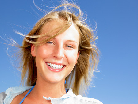 Woman smiling,  blue sky above Stock Photo