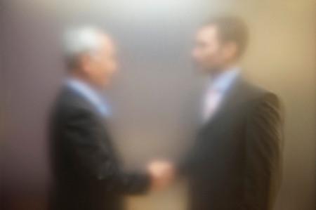 Men shaking hands behind screen