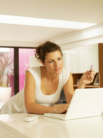 Woman using credit card with laptop
