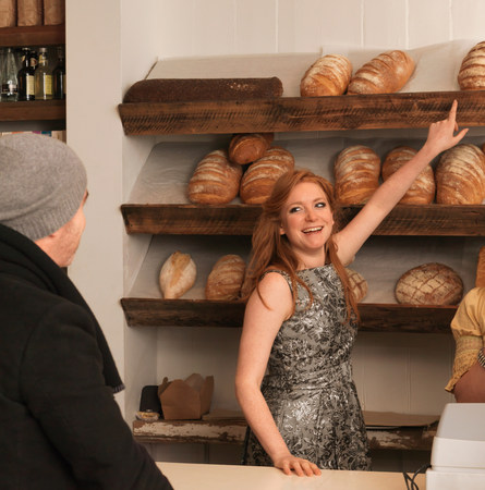 Woman pointing at bread on shelf Stock Photo