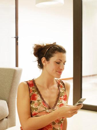 Woman sitting on floor,  texting