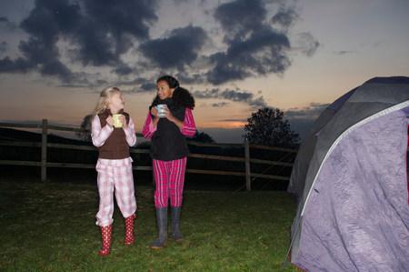 Girls walking to tent at dusk