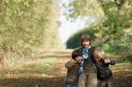 Three boys walking on country lane Stock Photo