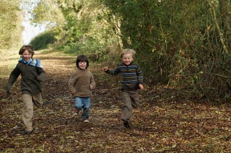 Boys running down country lane Stock Photo