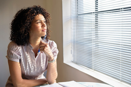 Young woman with pen poised, thinking Stock Photo
