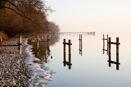 pier and icy lake in winter