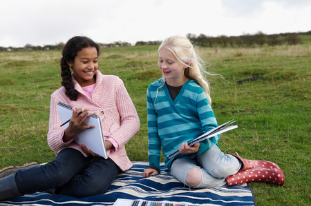 Two girls sketching on hillside